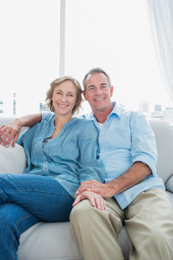Download Middle Aged Couple Sitting On The Couch Stock Photo - Image: 33053484