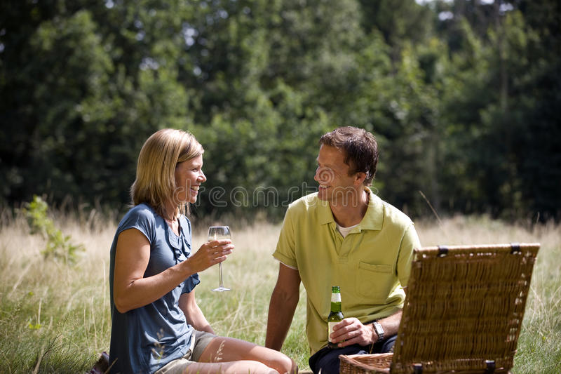 A middle aged couple sitting on the grass, having a drink stock images