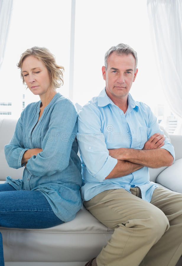 Middle aged couple sitting on the sofa not speaking after a dispute royalty free stock image