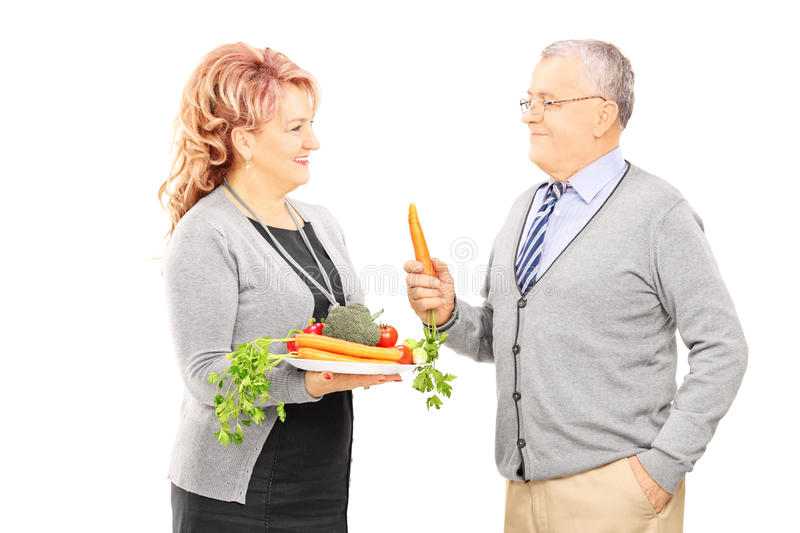 Middle aged couple standing close together and holding a healthy