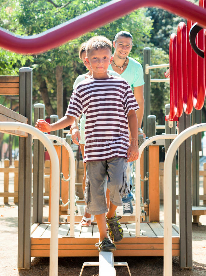 Middle-aged couple together with teenager overcomes the obstac. Le course on the playground in summer royalty free stock photos
