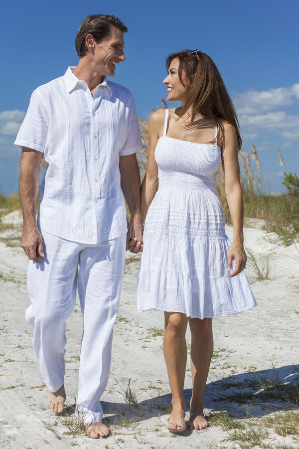 Middle Aged Couple Walking on An Empty Beach stock images