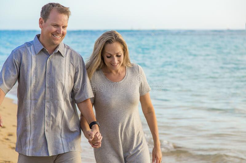 Middle aged couple walking together holding hands on the beach royalty free stock images
