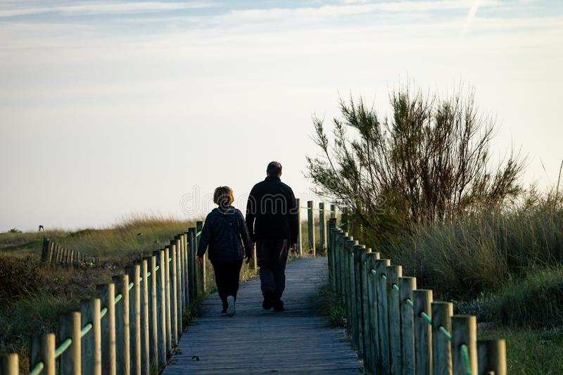 Middle-Aged Couple Walks on Boardwalk stock photos