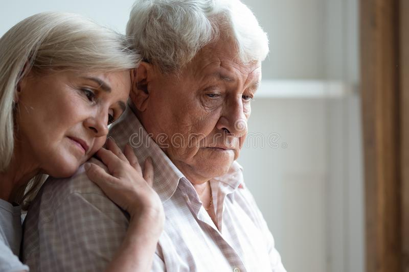 Middle-aged daughter snuggle to elderly father sharing his sorrows. Senior spouses remember sad moments of life together, middle-aged adult daughter snuggle up royalty free stock photos