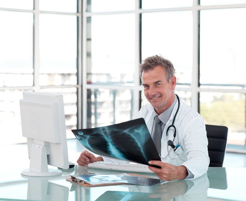 Middle aged doctor working at his Desk royalty free stock images
