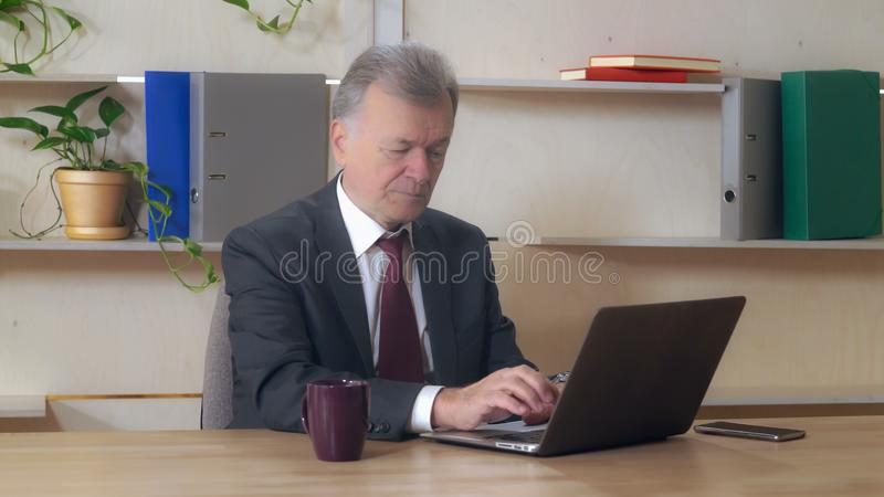 Middle aged entrepreneur using pc at work royalty free stock image