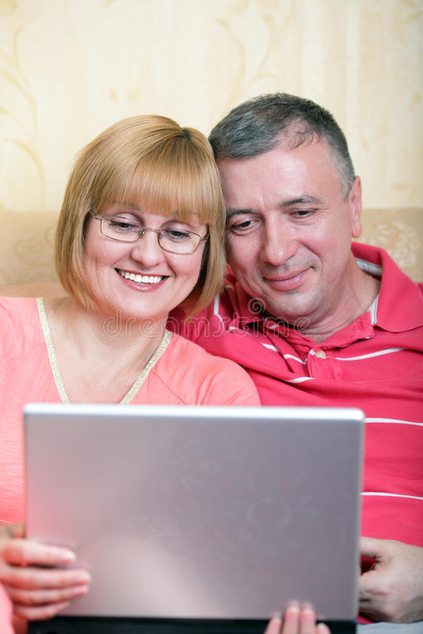 Middle-aged family surfing internet. Middle-aged family enjoying their life surfing the internet stock image