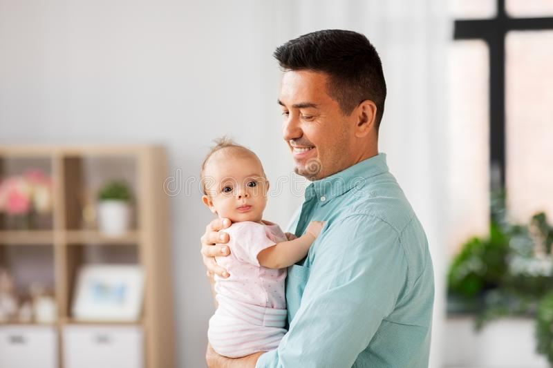 Middle aged father with baby daughter at home stock photos