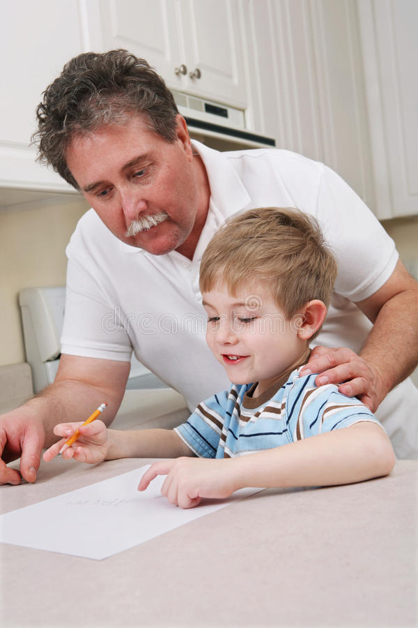 Middle aged father helping young son with homework royalty free stock images