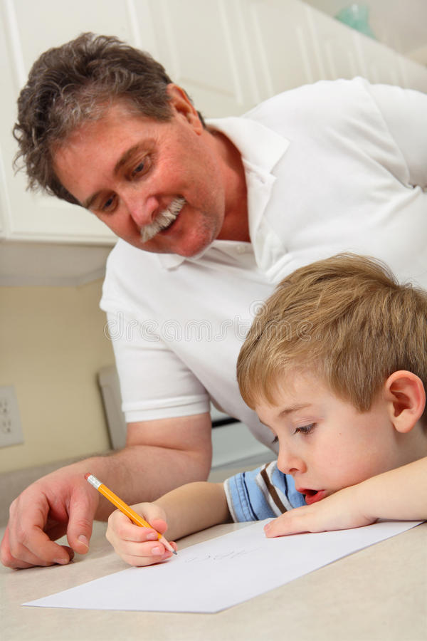 Middle aged father helping young son with homework stock photo