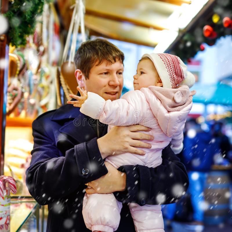 Middle aged father holding baby daughter near sweet stand with gingerbread and nuts. Happy family on Christmas market in. Germany. Cute girl eating cookie royalty free stock image