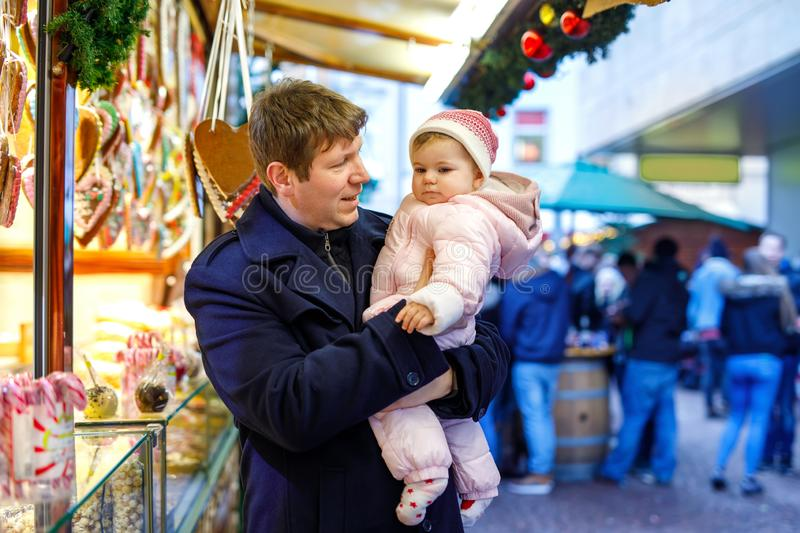 Middle aged father holding baby daughter near sweet stand with gingerbread and nuts. Happy family on Christmas market in. Germany. Cute girl eating cookie royalty free stock images