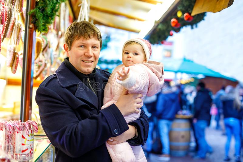 Middle aged father holding baby daughter near sweet stand with gingerbread and nuts. Happy family on Christmas market in. Germany. Cute girl eating cookie royalty free stock photos