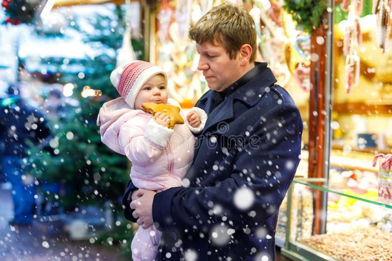 Middle aged father holding baby daughter near sweet stand with gingerbread and nuts. Happy family on Christmas market in. Germany. Cute girl eating cookie stock photos
