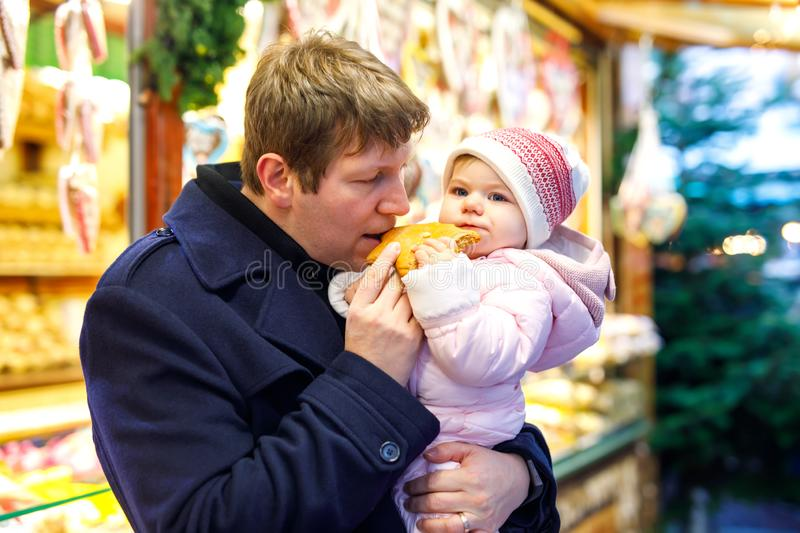 Middle aged father holding baby daughter near sweet stand with gingerbread and nuts. Happy family on Christmas market in. Germany. Cute girl eating cookie royalty free stock photography