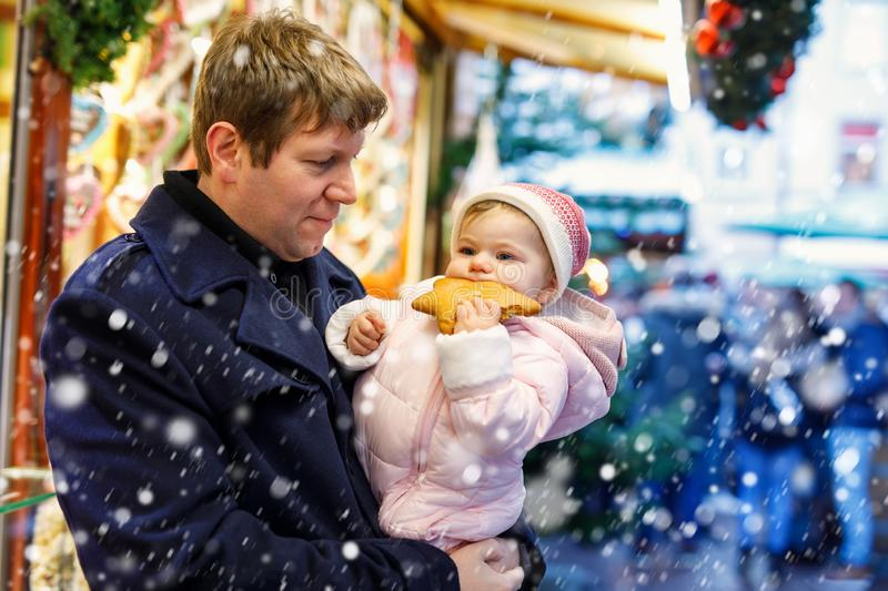 Middle aged father holding baby daughter near sweet stand with gingerbread and nuts. Happy family on Christmas market in. Germany. Cute girl eating cookie stock images