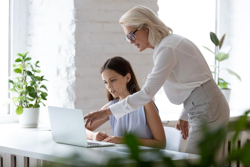 Middle-aged female boss explaining corporate application to new employee stock photos