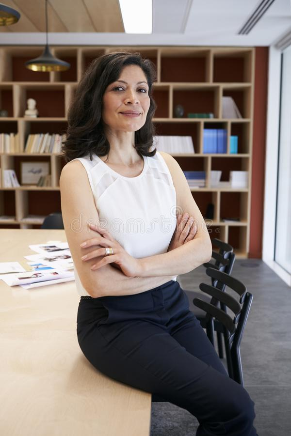 Middle aged female creative sitting on the desk in an office royalty free stock photo