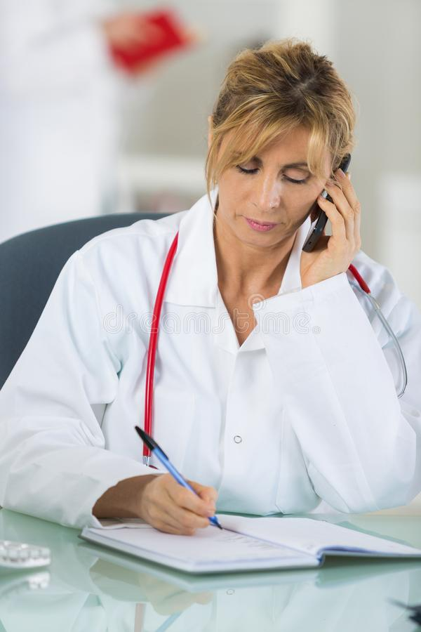 Middle-aged female doctor talking with patient on mobile phone royalty free stock photo