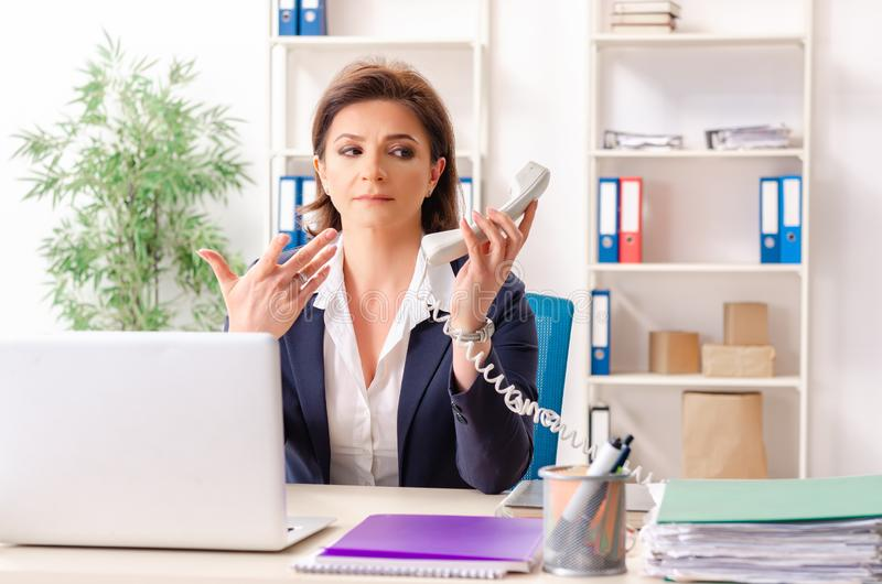The middle-aged female employee sitting at the office. Middle-aged female employee sitting at the office stock photo