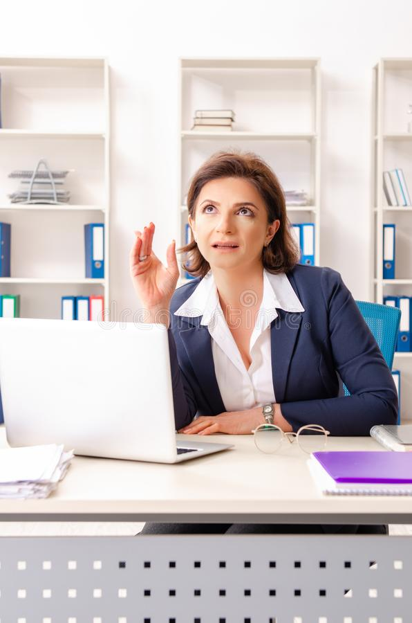 The middle-aged female employee sitting at the office. Middle-aged female employee sitting at the office stock photography