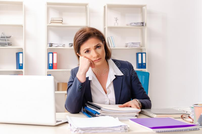 The middle-aged female employee sitting at the office. Middle-aged female employee sitting at the office royalty free stock images