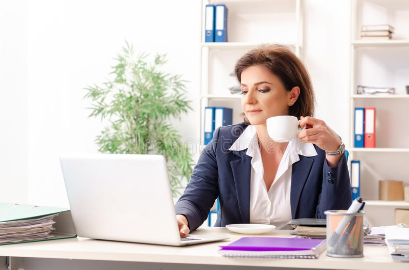 The middle-aged female employee sitting at the office. Middle-aged female employee sitting at the office royalty free stock image