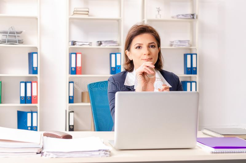 The middle-aged female employee sitting at the office. Middle-aged female employee sitting at the office stock photos