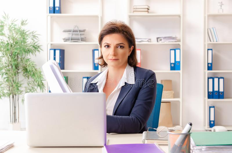 The middle-aged female employee sitting at the office royalty free stock images