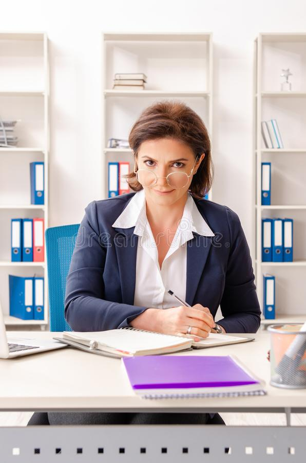 The middle-aged female employee sitting at the office. Middle-aged female employee sitting at the office royalty free stock photos