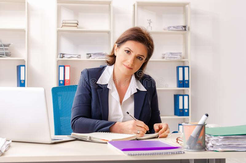 The middle-aged female employee sitting at the office stock photography
