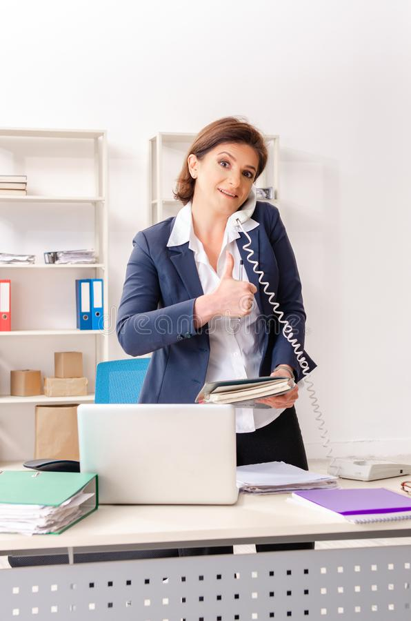 The middle-aged female employee sitting at the office. Middle-aged female employee sitting at the office royalty free stock photo