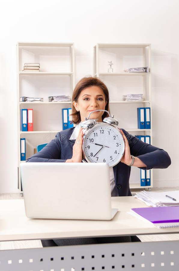 The middle-aged female employee sitting at the office. Middle-aged female employee sitting at the office stock images