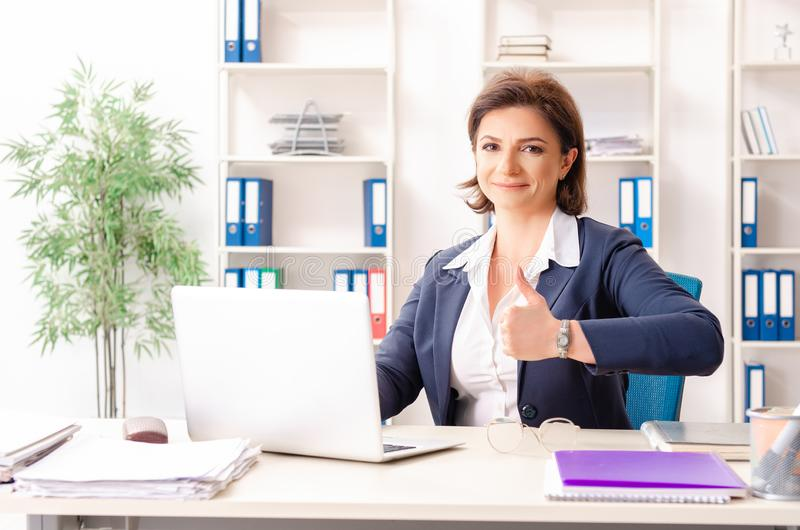 The middle-aged female employee sitting at the office. Middle-aged female employee sitting at the office stock image