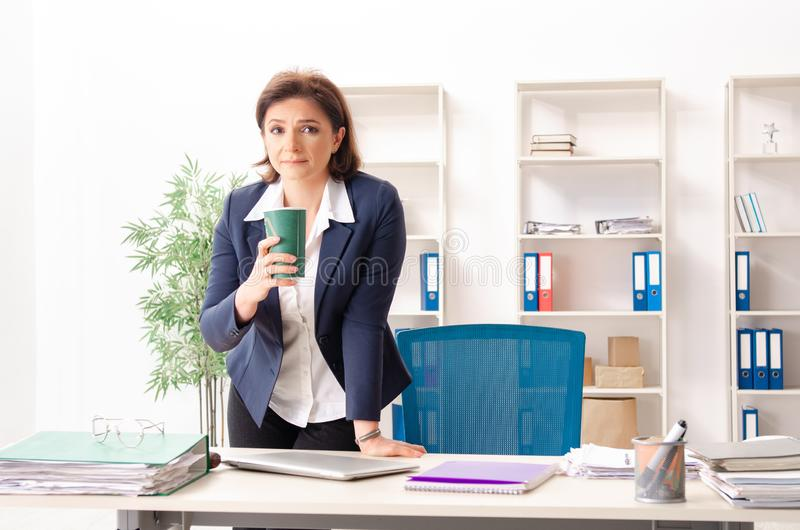 The middle-aged female employee sitting at the office. Middle-aged female employee sitting at the office royalty free stock photography