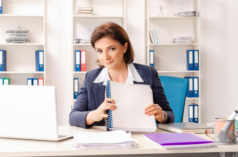 The middle-aged female employee sitting at the office stock photos
