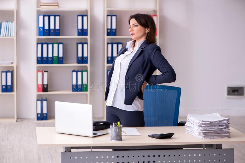 The middle-aged female employee suffering in the office stock photography