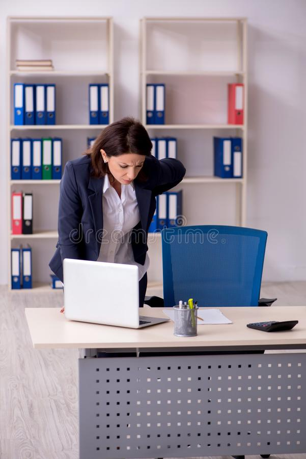 Middle-aged female employee suffering in the office stock photos