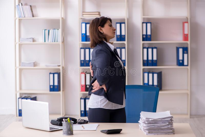 The middle-aged female employee suffering in the office stock photos
