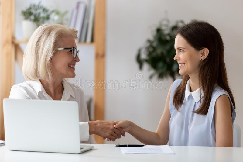 Aged employer congratulates young woman with job interview successful accomplishment. Middle-aged female employer congratulates young women with job interview royalty free stock image