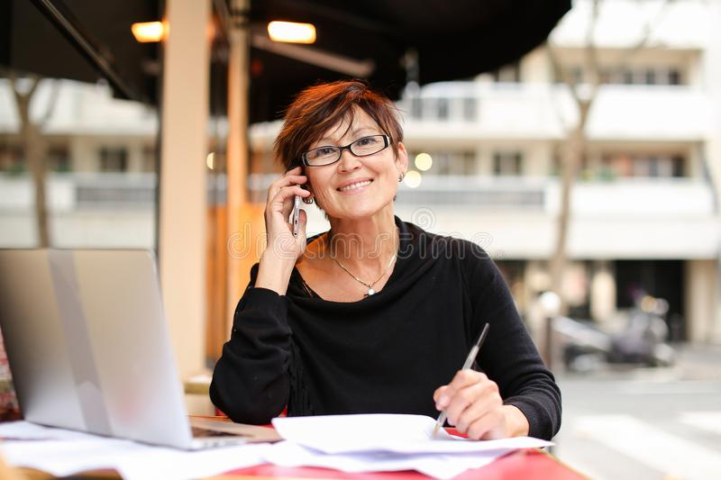 middle aged female extramural student using laptop for stock photo