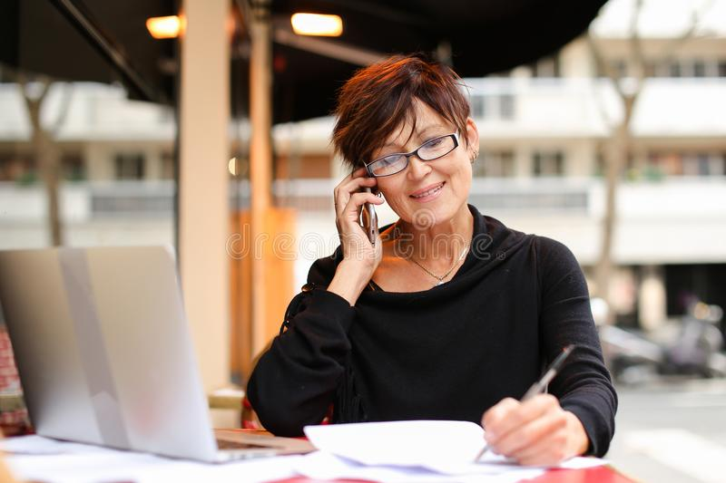 middle aged female extramural student using laptop for stock photos