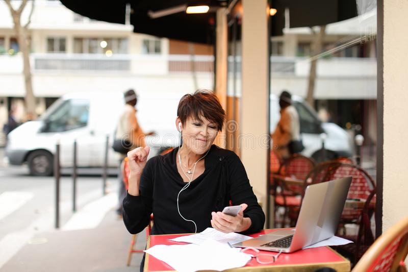 middle-aged female tourist listen music by smartphone and danci royalty free stock images