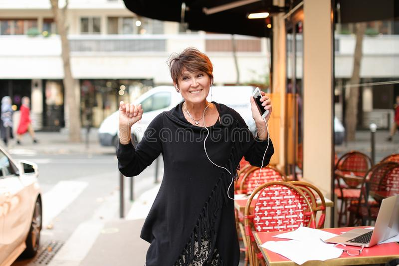 middle-aged female tourist listen music by smartphone and danci royalty free stock photos