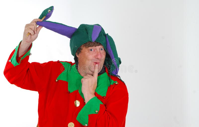 Middle aged fool. A portrait of a middle aged man dressed as a jester in a foolish pose and with a silly expression against a white background stock images
