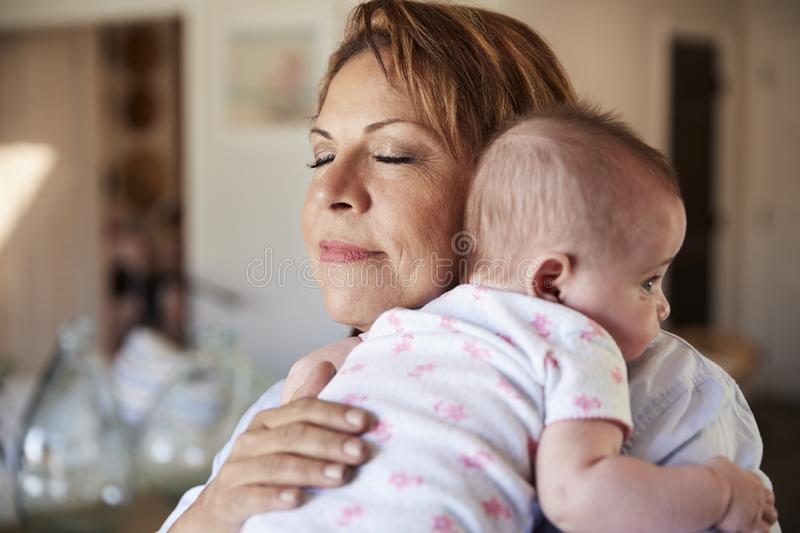 Middle aged grandmother with eyes closed holding her newborn grandson, head and shoulders, close up stock photo