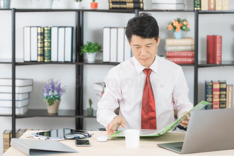 Asian business man at office. Middle aged, handsome, Asian, businessman, in white shirt, dark red necktie, working in his startup office, documents file and pen royalty free stock photos