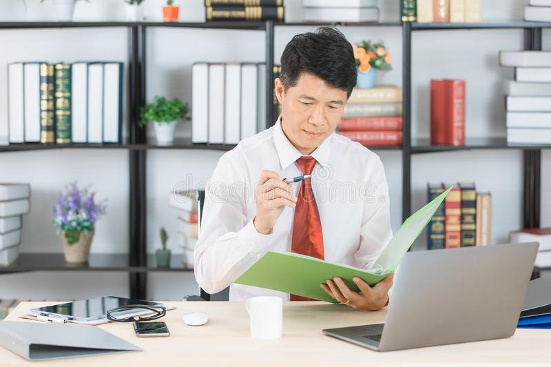 Asian business man at office. Middle aged, handsome, Asian, businessman, in white shirt, dark red necktie, working in his startup office, documents file and pen stock photography