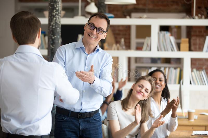 Middle aged boss, mentor congratulating employee, shaking hand. Middle aged happy smiling boss, mentor congratulating employee, praise for good work, new project royalty free stock photography